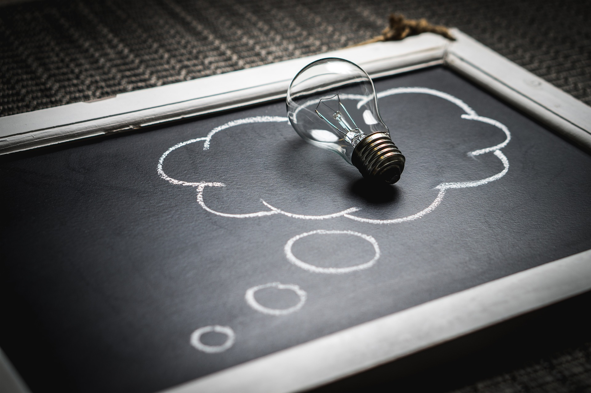 A light bulb placed on top of a blackboard with a thought bubble drawn in chalk