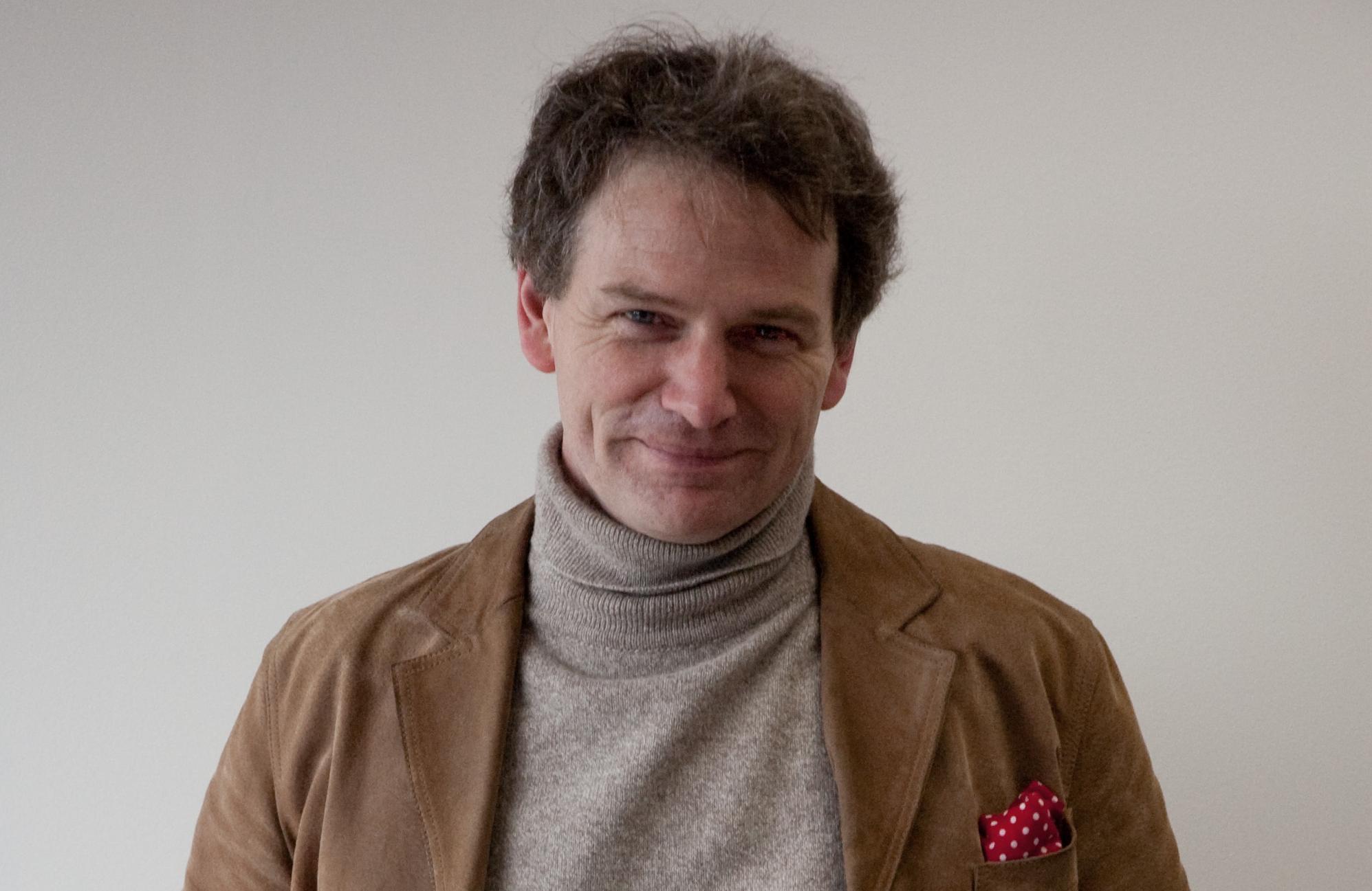 Smiling man in turtleneck jumper against a white background