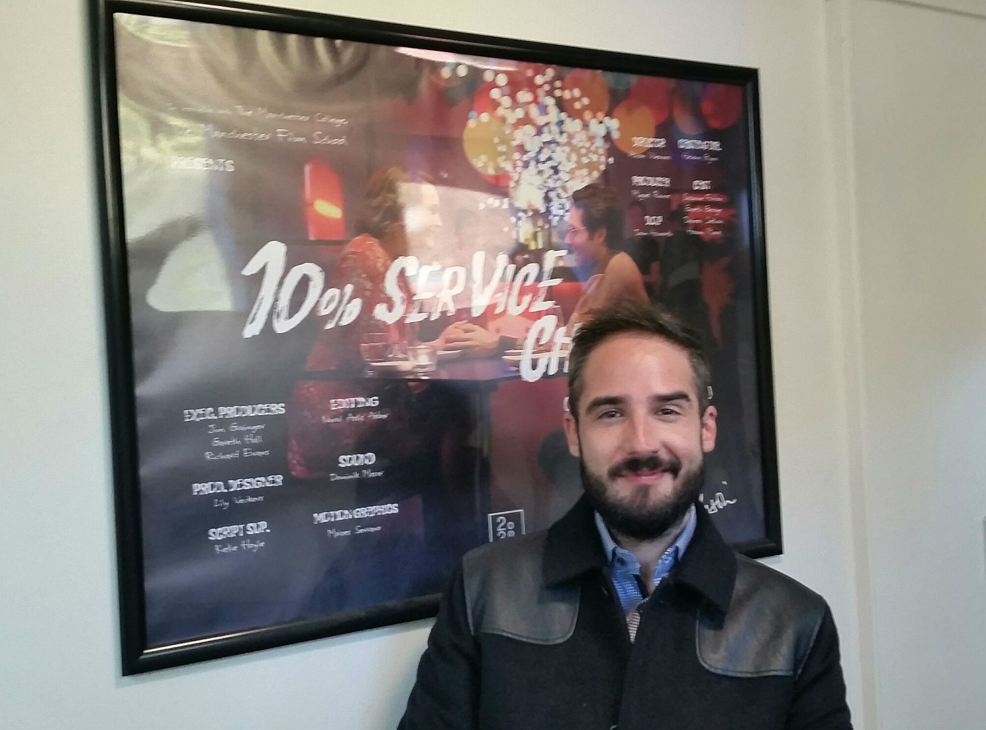 Man smiles infront of movie poster