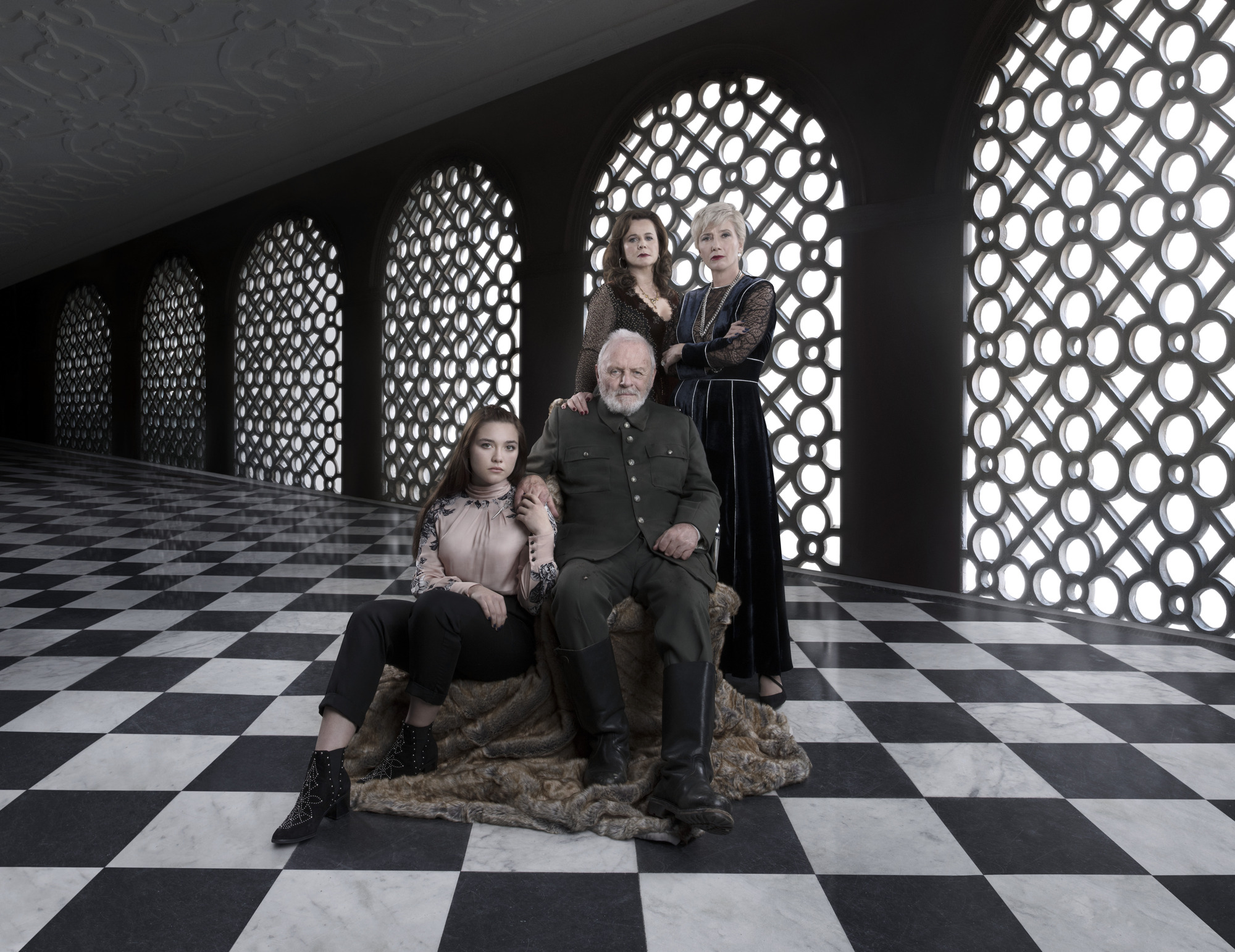 King Lear on his throne as his daughters surround him