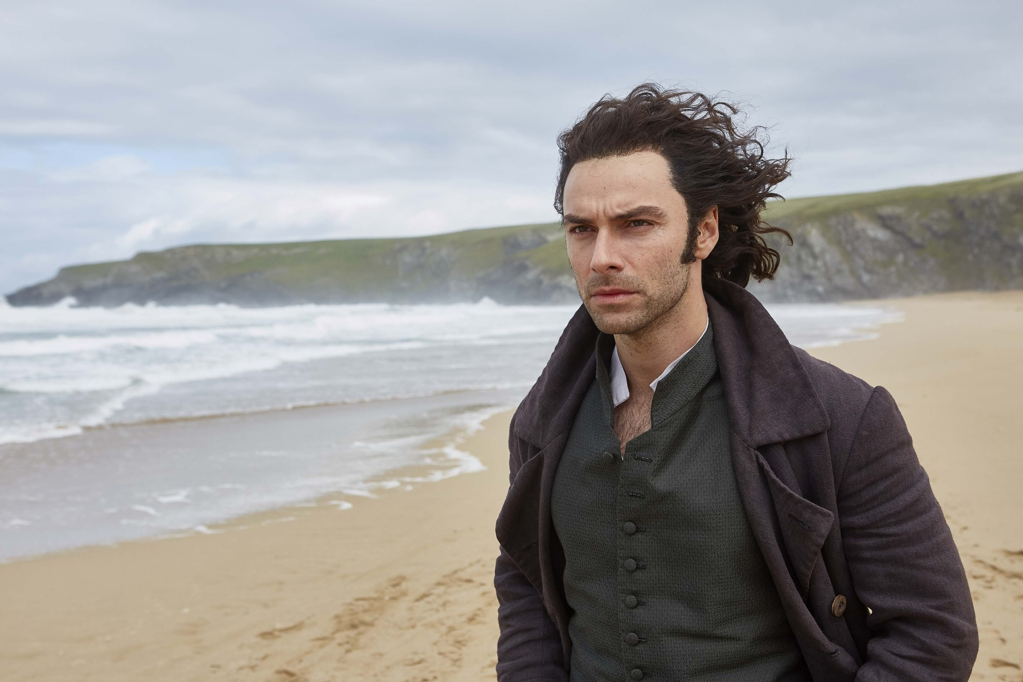 The actor Aidan Turner, playing Poldark on a windswept beach