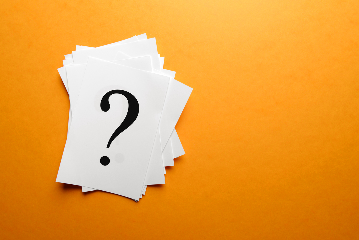 Question mark on white paper with a bright orange background